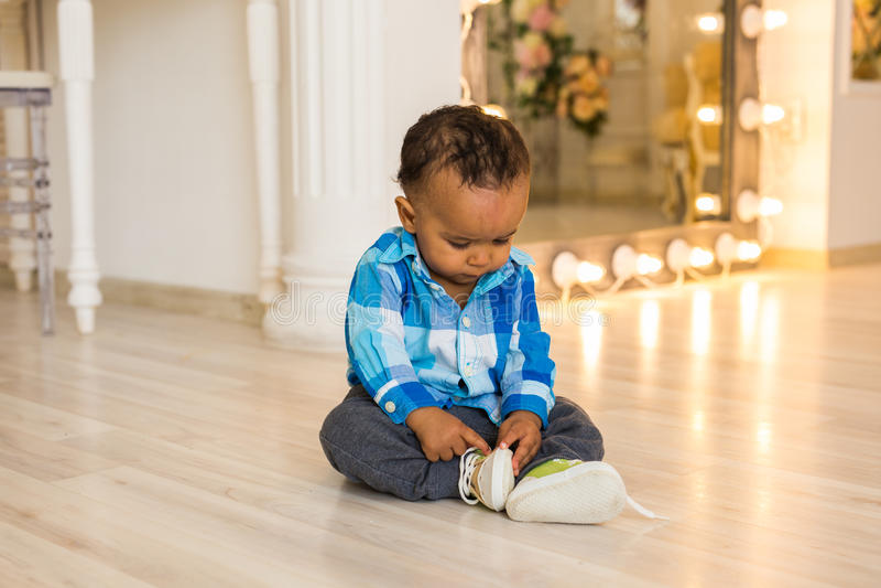 A criança pequena tenta põr sobre suas sapatas Bebê da raça misturada com sapatas imagem de stock royalty free