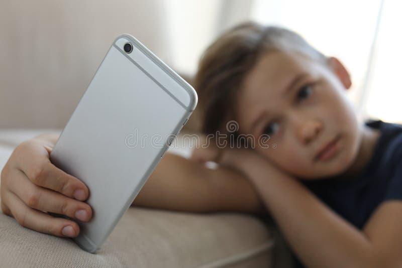 Criança pequena triste com o smartphone que inclina-se no sofá Perigo do Internet imagem de stock royalty free