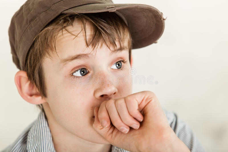 Criança pobre ansiosa com mão perto da boca foto de stock