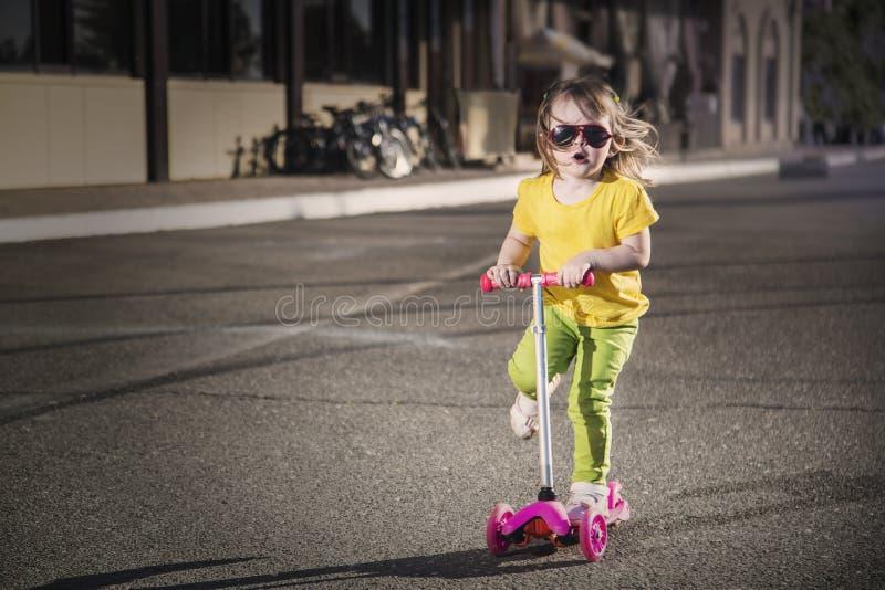 Criança positiva feliz no 'trotinette' na cidade imagens de stock royalty free
