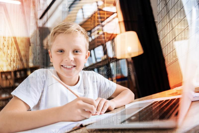 Criança positiva que sente contente ao fazer anotações na frente de um portátil fotos de stock royalty free