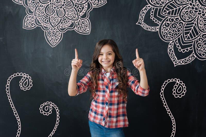 Criança positiva que sorri e que aponta às imagens na parede imagem de stock royalty free