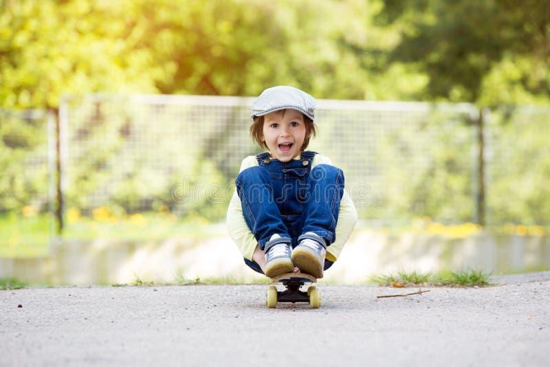 Criança pré-escolar adorável, skateboarding na rua imagens de stock