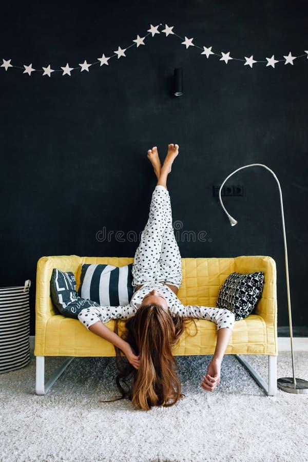 Criança pre adolescente no sofá contra a parede preta na vida moderna foto de stock royalty free