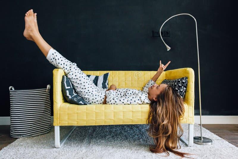 Criança pre adolescente no sofá contra a parede preta na vida moderna imagem de stock