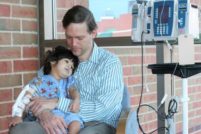 Criança preocupada da terra arrendada do pai no hospital imagens de stock royalty free