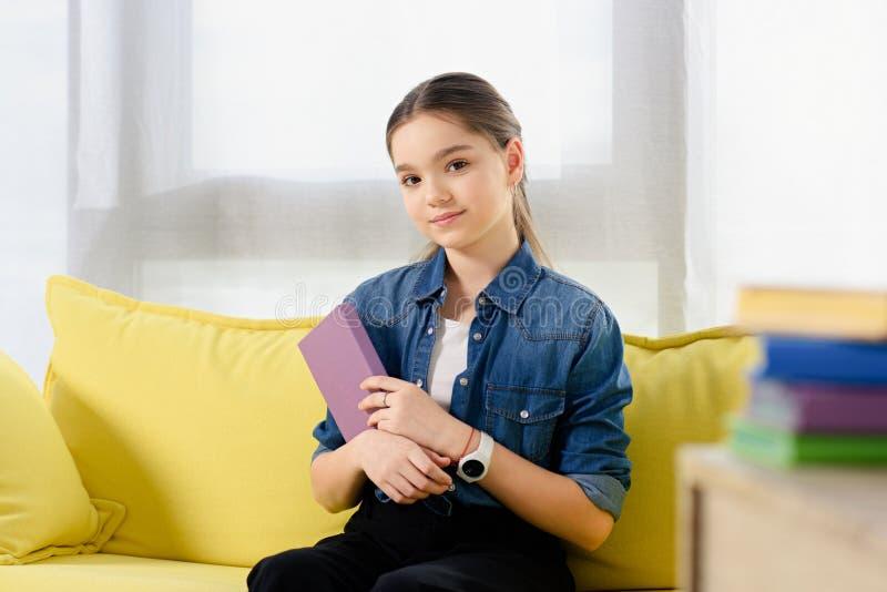 criança preteen adorável que senta-se com o livro violeta no sofá fotografia de stock royalty free