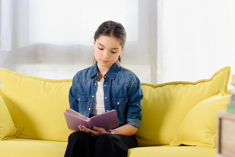 criança preteen adorável que senta-se no sofá e no livro de leitura amarelos foto de stock