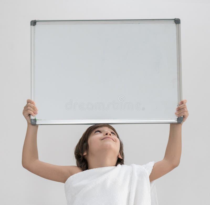 Criança pronta para o Haj que guarda a placa branca do espaço da cópia foto de stock