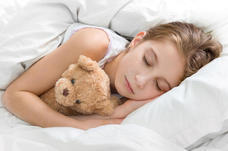Criança que abraça seu urso de peluche no sono fotografia de stock