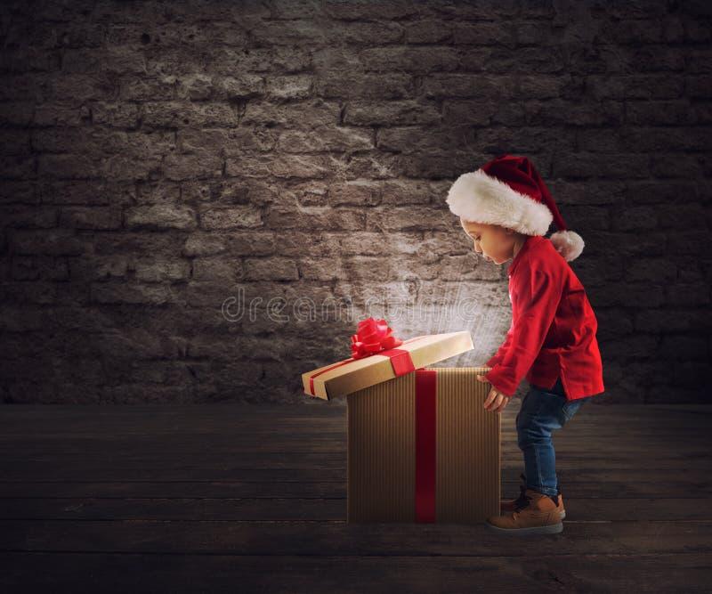 Criança que abre um presente mágico do Natal imagens de stock royalty free