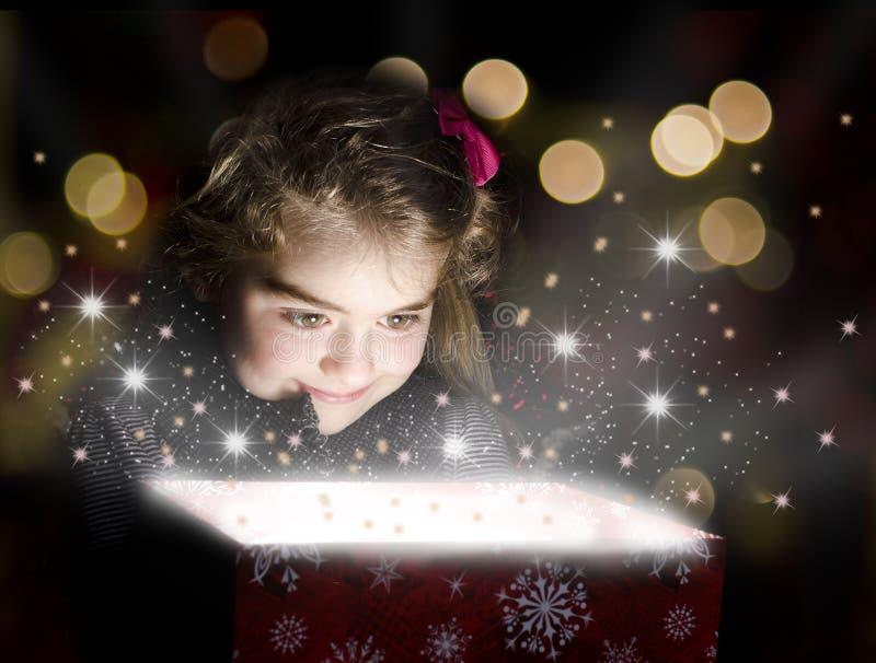 Criança que abre uma caixa de presente mágica imagem de stock royalty free