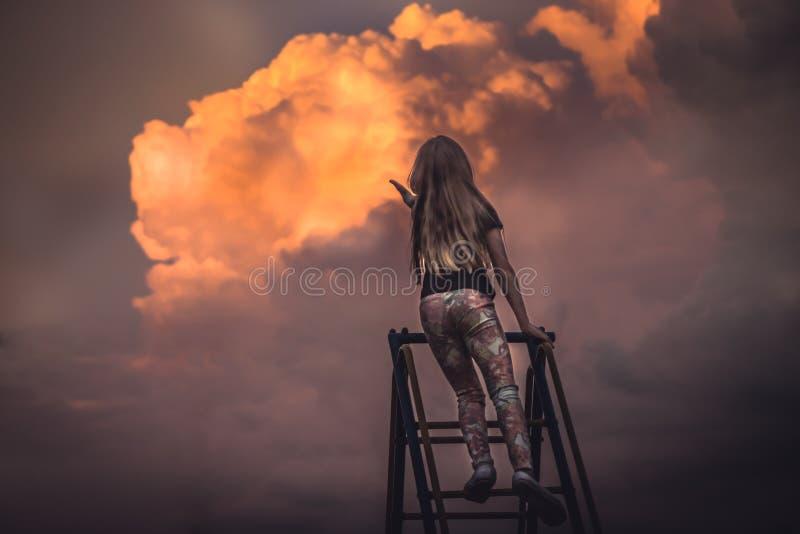 Criança que admira o por do sol cênico com nuvens bonitas e que alcança para fora as mãos ao céu imagem de stock royalty free