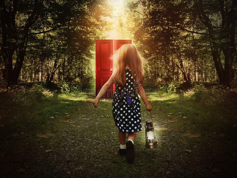 Criança que anda nas madeiras à porta vermelha de incandescência fotos de stock royalty free