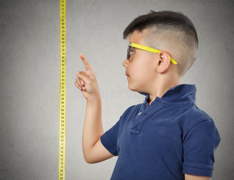 Criança que aponta em sua altura na fita de medição imagem de stock royalty free