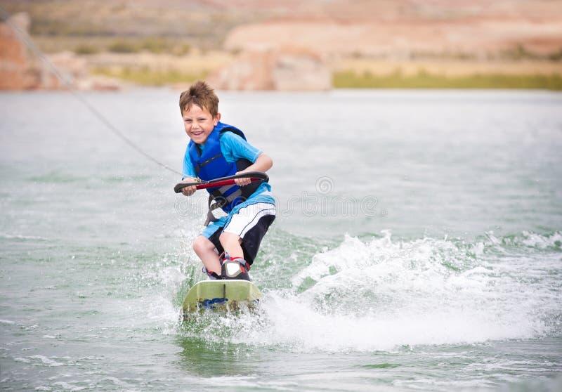 Criança que aprende ao wakeboard fotos de stock royalty free