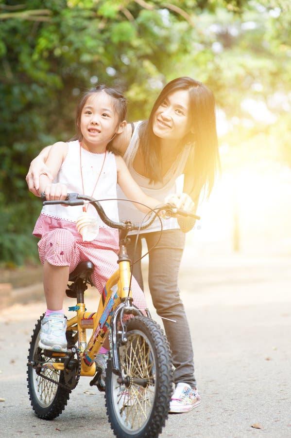 Criança que aprende bike com a ajuda da mãe exterior foto de stock