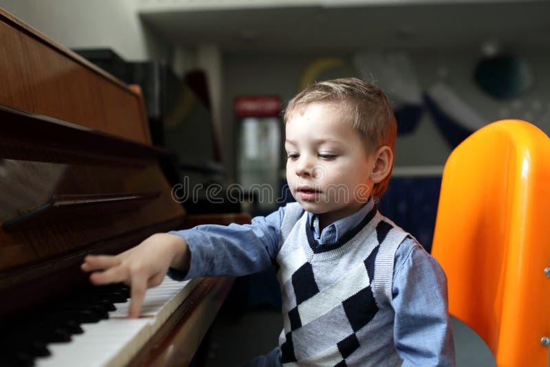 Criança que aprende jogar o piano imagens de stock
