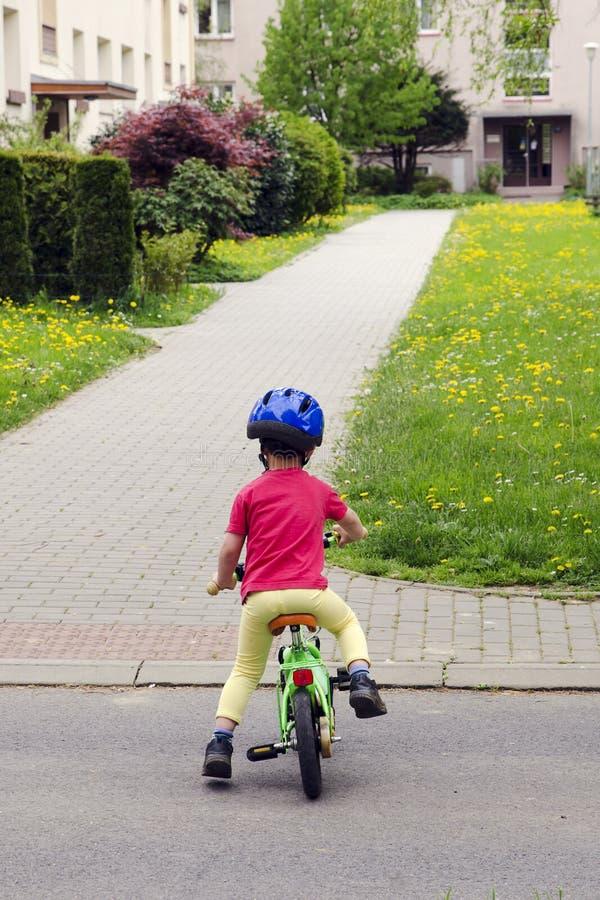 Criança que aprende montar uma bicicleta imagem de stock