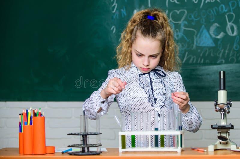 Criança que aprende a química no laboratório Crianças felizes Lição da química os estudantes fazem experiências da biologia com m imagem de stock royalty free
