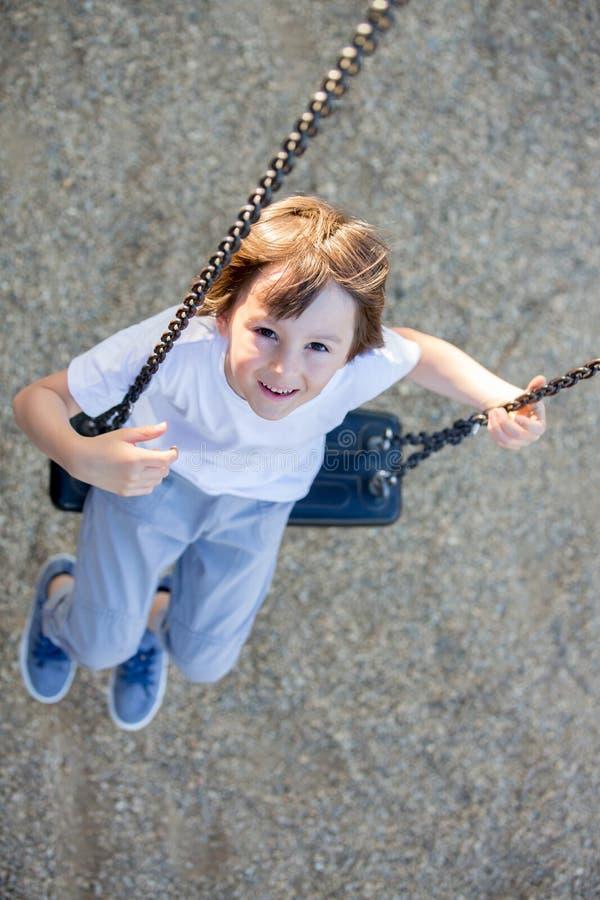 Criança que balança no campo de jogos foto de stock