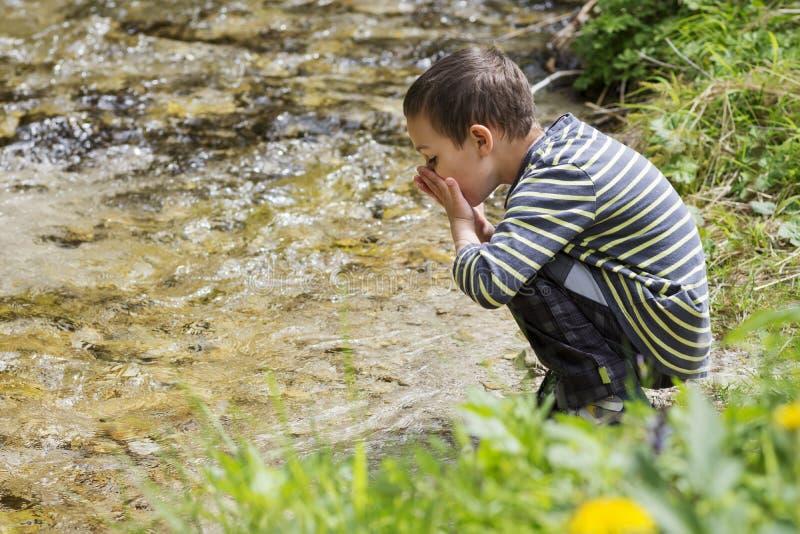 Criança que bebe a água do rio limpa foto de stock