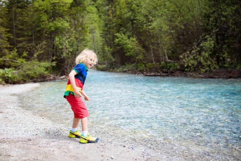 Criança que caminha nas montanhas Crianças na costa do rio foto de stock