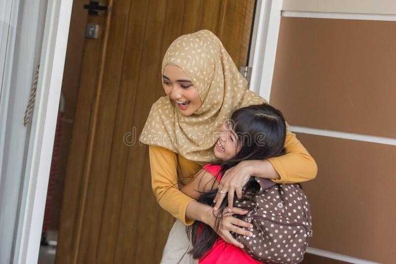 Criança que chegam em casa e mamã do abraço imagem de stock