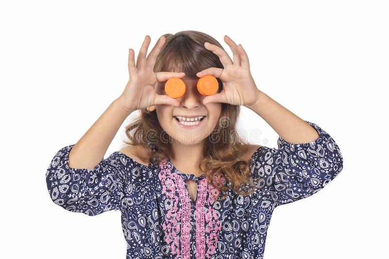 Criança que cobre seus olhos com as cenouras, promovendo hábitos comendo saudáveis em uma idade nova imagens de stock