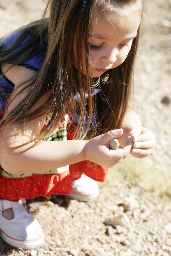 Criança que coleta rochas foto de stock