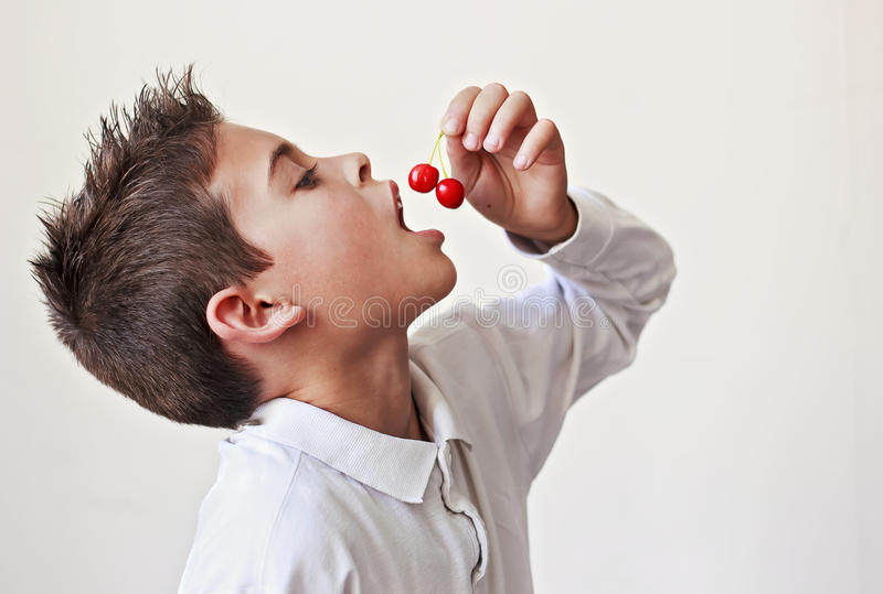 Criança que come cerejas fotos de stock
