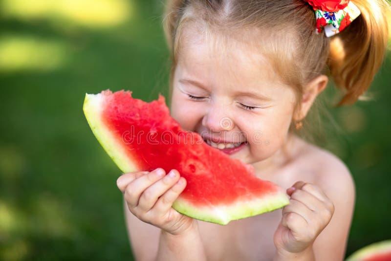 criança que come a melancia no jardim As crianças comem o fruto fora Petisco saudável para crianças Menina que joga na posse do j imagens de stock