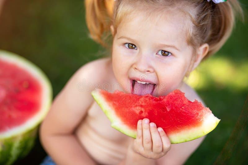 criança que come a melancia no jardim As crianças comem o fruto fora Petisco saudável para crianças Menina que joga na posse do j fotos de stock