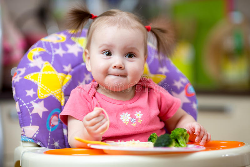 Criança que come o alimento na cozinha fotos de stock royalty free