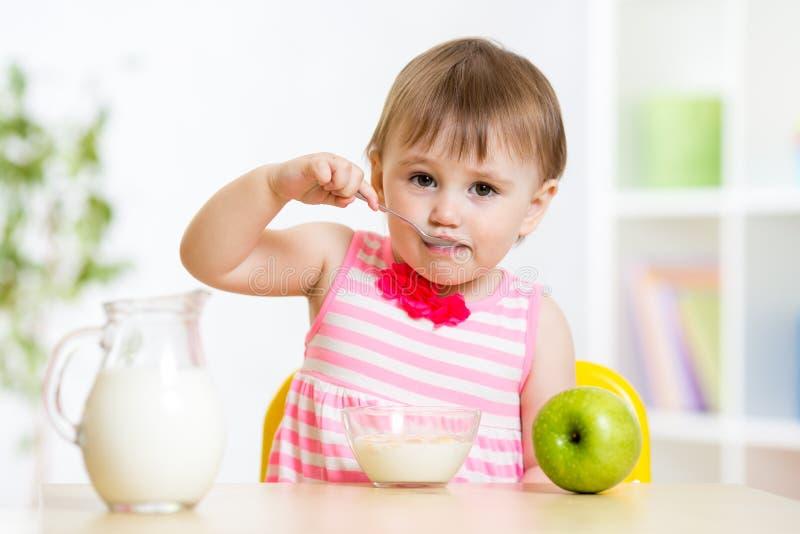 Criança que come o alimento próprio com colher imagens de stock royalty free