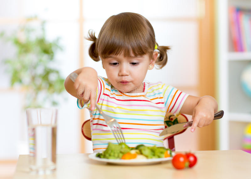 Criança que come o alimento saudável em casa ou o jardim de infância imagens de stock royalty free