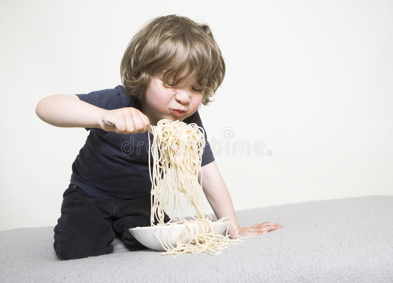 Criança que come os espaguetes no sofá foto de stock