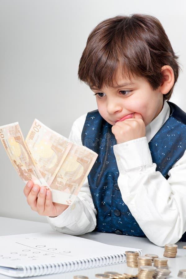 Criança que conta o dinheiro imagens de stock