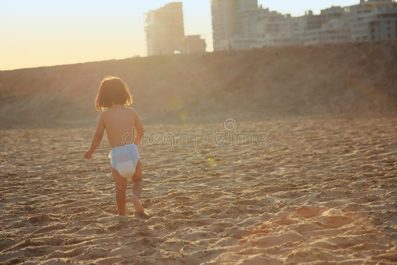 Criança que corre na areia no por do sol fotografia de stock royalty free
