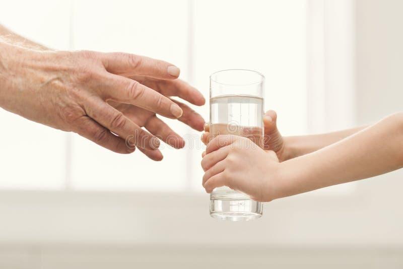 Criança que dá o vidro da água ao mgrandfather foto de stock royalty free