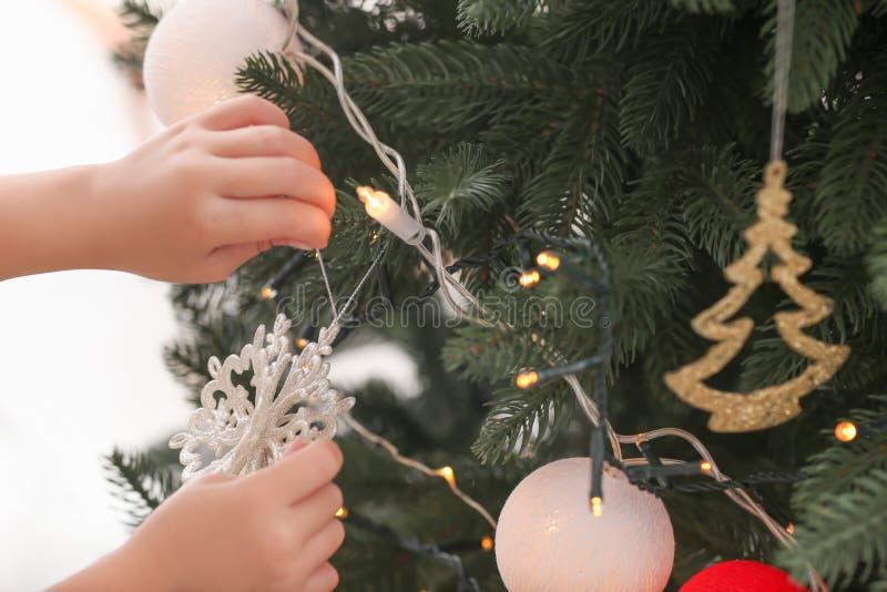 Criança que decora a árvore de Natal, close up fotos de stock royalty free