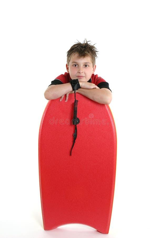 Criança que descansa com um bodyboard foto de stock royalty free