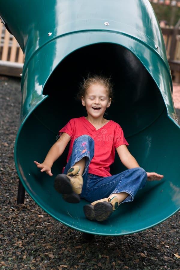 Criança que desliza no campo de jogos. fotos de stock