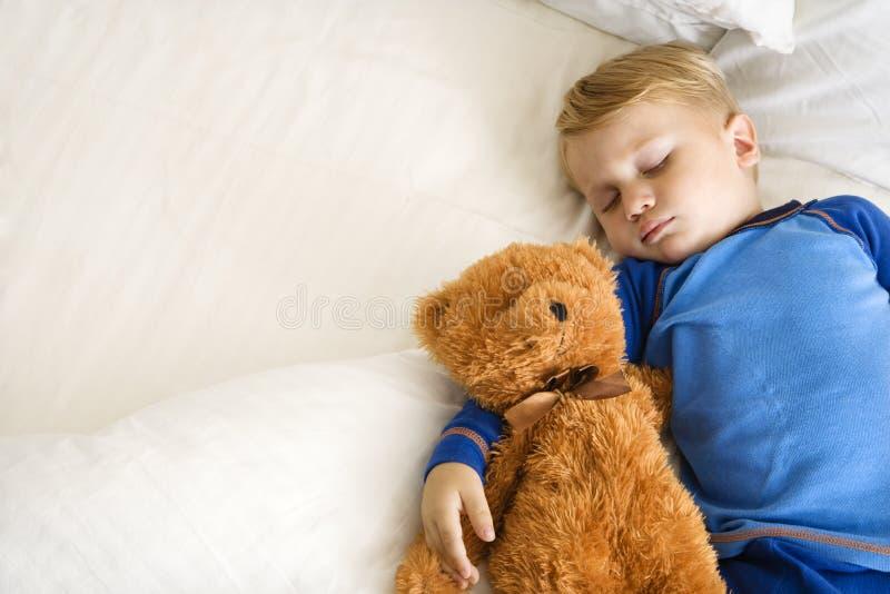 Criança que dorme com urso. imagens de stock