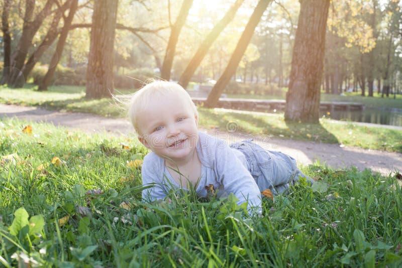 Criança que encontra-se na grama verde exterior fotografia de stock royalty free