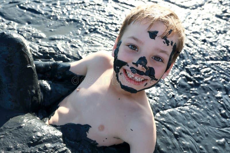 Criança que encontra-se na lama cura foto de stock