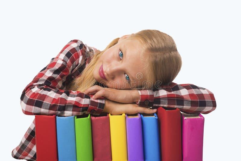 Criança que encontra-se na pilha dos livros fotos de stock
