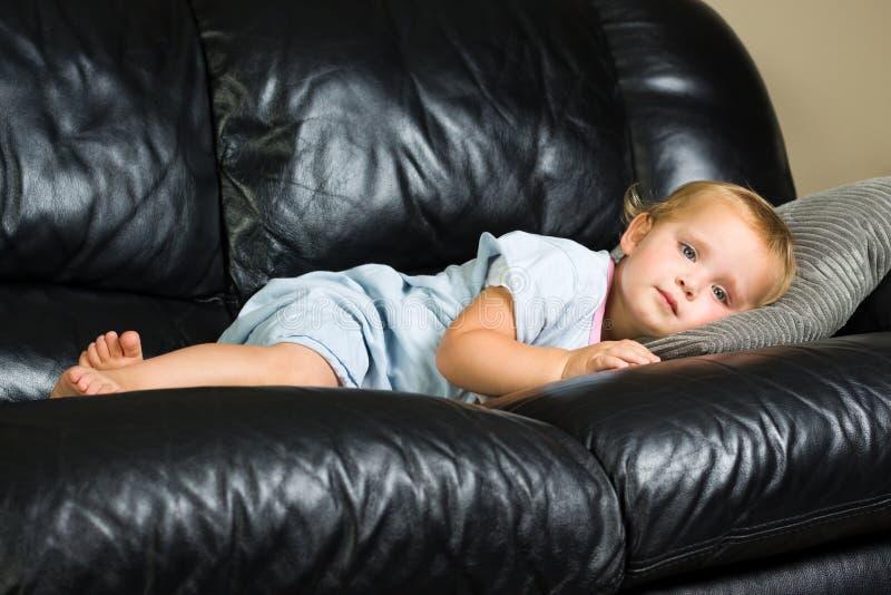 Criança que encontra-se no sofá fotografia de stock royalty free