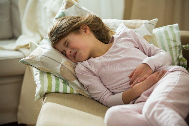 Criança que encontra-se no sofá na sala de visitas com dor de estômago foto de stock