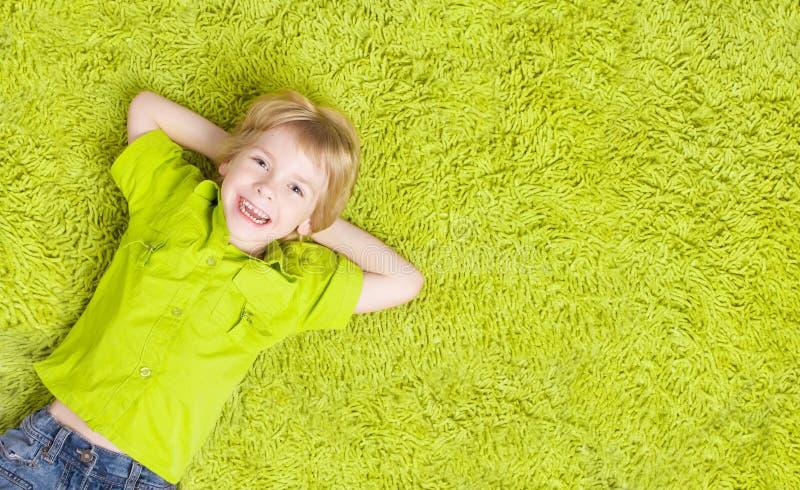 Criança que encontra-se sobre o tapete verde Menino de sorriso feliz da criança imagens de stock